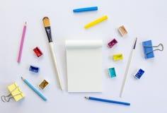Инструменты блокнота и искусства на белой предпосылке Стоковое Изображение