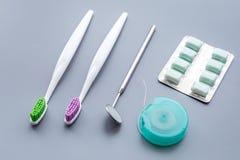 Инструменты для гигиены ротовой полости Щетки, зубочистка, зубоврачебное зеркало, камедь на голубой предпосылке стоковое фото