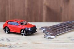 Инструменты для ремонта и завинчивать гайки хрома на таблице рядом с игрушкой стоковые изображения rf