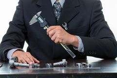 Инструменты и инженер-механик работая с много затягивая ключ и держа цифровой вернир Стоковые Изображения RF