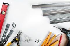 Инструменты и крепежные детали установки гипсокартона на белой предпосылке стоковые изображения