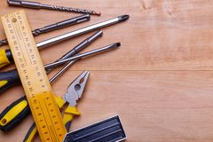 Инструменты и сверла лежат в левой стороне на деревянной предпосылке над взглядом Стоковое Фото