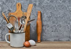 Инструменты кухни для варить на деревянном столе на предпосылке бетонной стены Стоковое Изображение