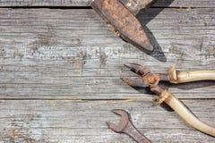 Инструменты на деревянных плоскогубцах молотка предпосылки и ключе открыт-конца стоковая фотография