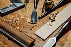 Инструменты на настольном компьютере в мастерской Делать скрипку Деревянные shavings и пыль, творческий беспорядок Стоковое фото RF
