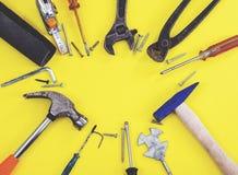 Инструменты на работниках джинсовой ткани, желтая предпосылка конструктора инженера ключа с инструментами конструктора инженера Н стоковая фотография