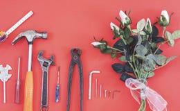 Инструменты на работниках джинсовой ткани, красная предпосылка конструктора инженера ключа с инструментами конструктора инженера  стоковая фотография rf