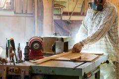 Инструменты плотника на деревянном столе с круглой пилой опилк Резать деревянную планку Стоковое Изображение RF