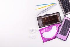 Инструменты расширения ресницы на белой предпосылке Аксессуары для расширений ресницы Искусственние плетки Взгляд сверху стоковое изображение rf