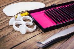 Инструменты расширения ресницы на деревянной предпосылке Аксессуары для расширений ресницы Искусственние плетки конец вверх стоковая фотография rf