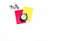 Инструменты рефери Желтые и красные карточки, секундомер, свисток на белом copyspace взгляд сверху предпосылки Стоковые Изображения