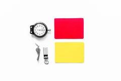 Инструменты рефери Желтые и красные карточки, секундомер, свисток на белом copyspace взгляд сверху предпосылки Стоковые Фото