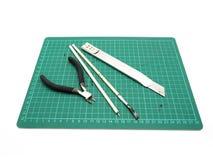 Инструменты с зеленой циновкой вырезывания для модельного набора изолированного на белом bac стоковые изображения rf