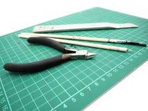 Инструменты с зеленой циновкой вырезывания для модельного набора изолированного на белом bac стоковое фото