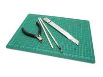 Инструменты с зеленой циновкой вырезывания для модельного набора изолированного на белом bac стоковая фотография