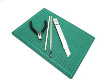 Инструменты с зеленой циновкой вырезывания для модельного набора изолированного на белом bac стоковое изображение rf