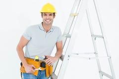 Инструменты удерживания работника пока полагающся на лестнице шага Стоковая Фотография