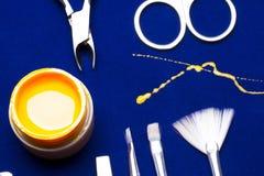 Инструменты для маникюра, желтого цвета цвета ногтя геля, грязного мастера сарая на голубой таблице упорно стоковые изображения rf