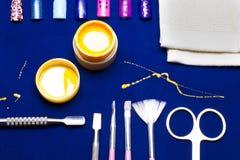 Инструменты для маникюра, желтого цвета цвета ногтя геля, грязного мастера сарая на голубой таблице упорно стоковая фотография rf