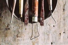 Инструменты для формировать глину с баками на деревянной предпосылке стоковая фотография rf
