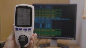 Инструмент метра силы, который держит молодой техник показывая потребление во время процесса bitcoin минируя - сток-видео