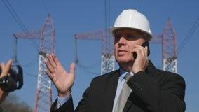 Интервью инженера используя сотовый телефон разговаривая с командой обслуживания стоковое фото