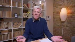 Интервью старшего человека спрашивая вопросы в камеру быть заинтересованный и восторженный на предпосылке книжных полка видеоматериал