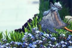 Интересная деталь на flowerbed кран металла среди цветков Небольшие голубые цветки растут в саде на солнечный день стоковое изображение