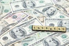 Интерес слова на куче банкнот доллара США Стоковая Фотография RF