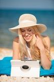 Интернет женщины занимаясь серфингом смотря таблетку на пляже Стоковое Фото