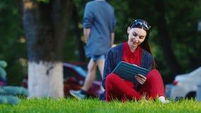 Интернет и прибор всегда с вами Женщина наслаждается таблеткой outdoors сток-видео