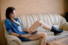 Интернет модной девушки занимаясь серфингом в офисе Стоковая Фотография