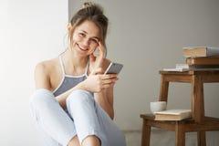 Интернет молодого красивого девочка-подростка занимаясь серфингом на телефоне усмехаясь смотрящ камеру сидя на поле среди старых  Стоковые Фотографии RF