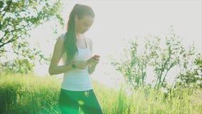 Интернет молодой женщины занимаясь серфингом используя ее smartphone внешний, в парке акции видеоматериалы