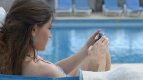Интернет просматривать милого брюнет женский на smartphone около бассейна видеоматериал