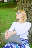 Интернет студента занимаясь серфингом в парке Студент подготавливает проект Исследование парка компьтер-книжки женщины онлайн Дев стоковые фото