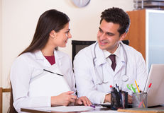 Интерн детенышей доктора советуя с в офисе клиники Стоковые Изображения