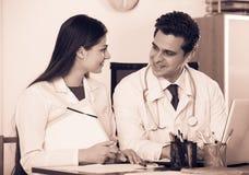 Интерн детенышей доктора советуя с в офисе клиники Стоковая Фотография