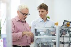 Интерн показа старшего инженера как рассмотреть принтер 3D стоковые фотографии rf