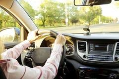 Интерьер автомобиля при женский водитель сидя за колесом, мягкий свет захода солнца Роскошная приборная панель и электроника кора стоковое изображение