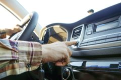 Интерьер автомобиля при мужской водитель сидя за колесом, мягкий свет захода солнца Роскошная приборная панель и электроника кора стоковое фото rf