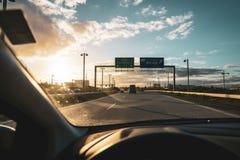 Интерьер автомобиля управляя на шоссе в заходе солнца стоковая фотография rf