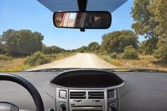 Интерьер автомобиля и дорога гравия на солнечный день Стоковая Фотография
