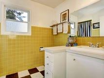 Интерьер ванной комнаты с белым шкафом, желтой плиткой на стенах и малым окном стоковое фото