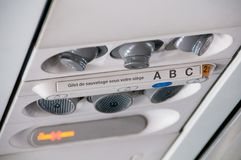 Интерьер внутренности самолета Надземная доска с знаком для некурящих и прикрепляет ремень безопасности, никто Голубой тон стоковое изображение rf