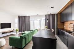 Интерьер гостиничного номера с зеленым салоном, телевизором, окнами с задрапировывает и угол кухни открытого пространства стоковые фото