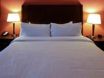 Интерьер гостиничного номера с сделанной кроватью и подушки с лампами дальше и красной стеной стоковые фотографии rf