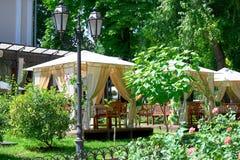 Интерьер кафа улицы в зеленом парке города, богато украшенном с цветками, сезоном лета, ярким солнечным днем Стоковое фото RF