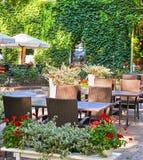 Интерьер кафа улицы лета в зеленом парке города, богато украшенном с цветками и декоративными элементами, белым зонтиком Стоковое Изображение