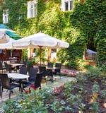 Интерьер кафа улицы лета с белым зонтиком в зеленом парке города, богато украшенном с цветками и декоративными элементами Стоковое фото RF
